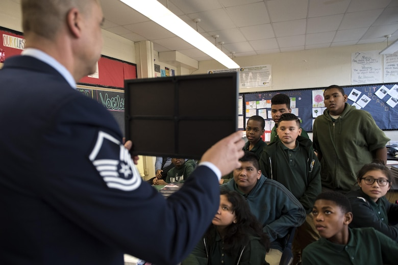 Master Sgt. David Gray, 113th Air National Guard security forces member, shows Charles Carroll Middle School students a photo during their Career and Technical Education Fair in New Carrollton, Md., Dec. 21, 2016. Gray had photos of him previously in the Army, on deployment and shaking hands with the Chairman of the Joint Chiefs of Staff Gen. Colin Powell. (U.S. Air Force photo by Senior Airman Philip Bryant)