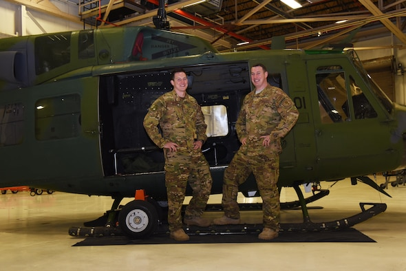 Tech. Sgt. Justin Nissen and Staff Sgt. Timothy Nissen, 37th Helicopter Squadron UH-1N helicopter flight engineers, pose next to a helicopter at F.E. Warren Air Force Base, Wyo., Dec. 12, 2016. After four years of trying, the brothers managed to get stationed together in the same unit. (U.S. Air Force photo by Airman 1st Class Breanna Carter)