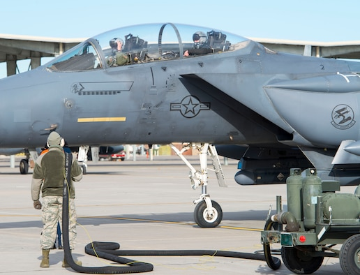 A member of the 366th Logistics Readiness Squadron fuels flight stands by to refuel an F-15E Strike Eagle during hot pit operations Nov. 16, 2016 at Mountain Home Air Force Base, Idaho. The 366th LRS fuels flight, also known as the petroleum, oil and lubricant flight, supports and maintains around 4.3 million gallons of fuel for the Fighter Wing, roughly equivalent fo six-and-a-half Olympic-sized swimming pools. (U.S. Air Force photo by 1st Lieutenant Kip Sumner/Released)