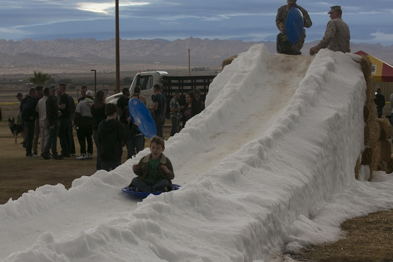 Children slide down a man-made snow hill during the 1st Battalion, 7th Marine Regiment Family Day at Del Valle Field aboard Marine Corps Air Ground Combat Center Twentynine Palms, Calif., Dec. 15, 2016. (Official Marine Corps photo by Cpl. Thomas Mudd/Released)