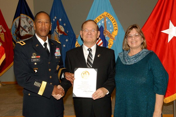 Army Brig. Gen. Charles Hamilton, DLA Troop Support commander, presents Russ Brooks, Subsistence field representative, with a certificate of retirement during a ceremony Dec. 15. Brooks was accompanied by his wife Denise, whom he thanked for standing beside him during his career.