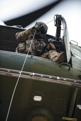 Staff Sgt. Travis Akerson, 37th Helicopter Squadron flight engineer, guides down a hoist to a training target 50 feet below the helicopter during search and rescue training at F.E. Warren Air Force Base, Wyo., Dec. 16. 2016. The 37th HS assists local civilian law enforcement with with SAR operations and airlift medical evacuations in Wyoming, Colorado and Nebraska. (U.S. Air Force photo by Staff Sgt. Christopher Ruano)
