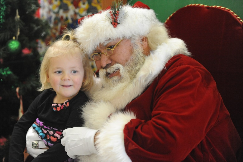 Santa Claus visits with a young child at Operation Holiday Cheer, one of Kirtland's biggest charitable events of the year. The event, hosted annually by the Kirtland Air Force Base Fire Department, delivered more than 800 new, high-quality toys to children Dec. 14.  More than 1,700 members of the community received a full holiday meal, with turkey, enchiladas, posole, mashed potatoes and desserts.