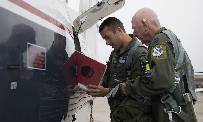 Capt. Steven Parsons, 47th Student Squadron assistant director of operations, and Jerry Yellin, author and retired U.S. Army Air Corps Captain, go over the aircraft forms before their flight in a T-6A Texan II on Laughlin Air Force Base, Texas, Dec. 15, 2016. The aircraft forms include all maintenance performed on the aircraft. (U.S. Air Force photo/Senior Airman Ariel D. Partlow)