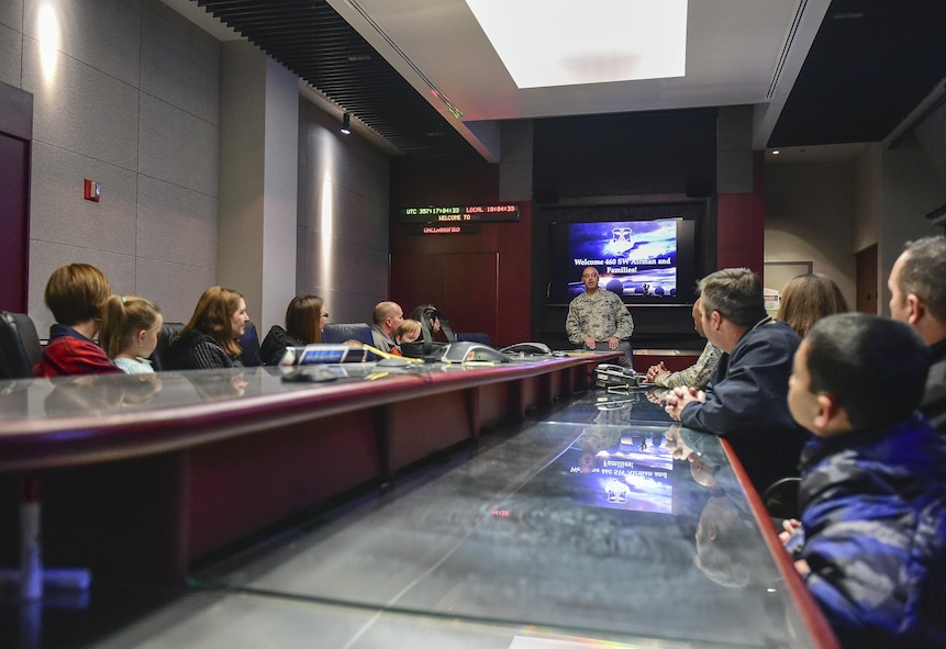 Col. David Miller Jr., 460th Space Wing commander, explains how missile warning the mission is accomplished during at Team Buckley Spouse and Family Day at the Mission Control Center on Buckley AFB, Colo., Dec. 22, 2016. The event consisted of families given access to see the 460th Space Wing mission up close, with demonstrations from the operators, Defenders, and firefighters. (U.S. Air Force photo by Tech. Sgt. Nicholas Rau/Released)