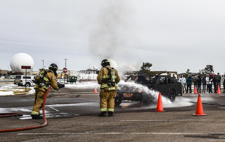 Buckley Firefighters, Andrew Gard and Jason Debord, put out a fire during a live experience at Team Buckley Spouse and Family Day at the Base Chapel on Buckley AFB, Colo., Dec. 22, 2016. The event consisted of families given access to see the 460th Space Wing mission up close, with demonstrations from the operators, Defenders, and firefighters. (U.S. Air Force photo by Tech. Sgt. Nicholas Rau/Released)