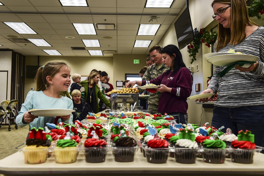 Attendees of the Team Buckley Spouse and Family Day fill their plates with a meal provided by the Base Chapel on Buckley AFB, Colo., Dec. 22, 2016. The event consisted of families given access to see the 460th Space Wing mission up close, with demonstrations from the operators, Defenders, and firefighters. (U.S. Air Force photo by Tech. Sgt. Nicholas Rau/Released)