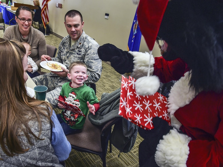 Luke receives a surprise gift from Buck Lee, six-star general and Buckley Air Force Base mascot, after finishing a cupcake during Team Buckley Spouse and Family Day at the Base Chapel on Buckley AFB, Colo., Dec. 22, 2016. The event consisted of families given access to see the 460th Space Wing mission up close, with demonstrations from the operators, Defenders, and firefighters. (U.S. Air Force photo by Tech. Sgt. Nicholas Rau/Released)