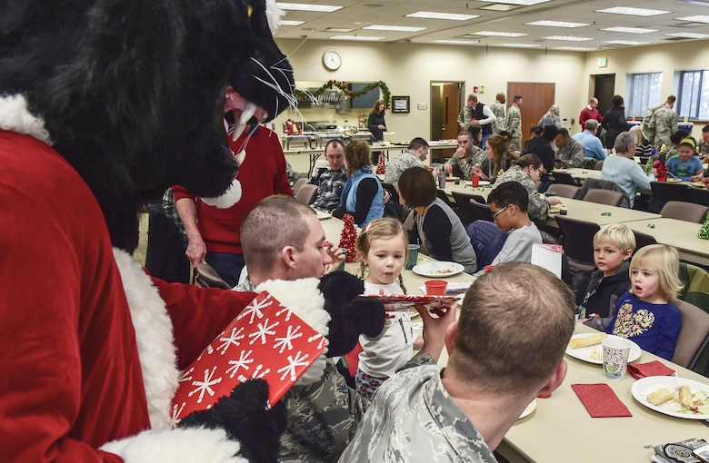 A child receives a surprise gift from Buck Lee, six-star general and Buckley Air Force Base mascot, as others look on in amazement during Team Buckley Spouse and Family Day at the Base Chapel on Buckley AFB, Colo., Dec. 22, 2016. The event consisted of families given access to see the 460th Space Wing mission up close, with demonstrations from the operators, Defenders, and firefighters. (U.S. Air Force photo by Tech. Sgt. Nicholas Rau/Released)