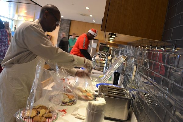 George Gray (left) and James Reed (background) bag cookies at the Warrior and Family Center, Fort Belvoir, Virginia, Dec. 21, 2016.