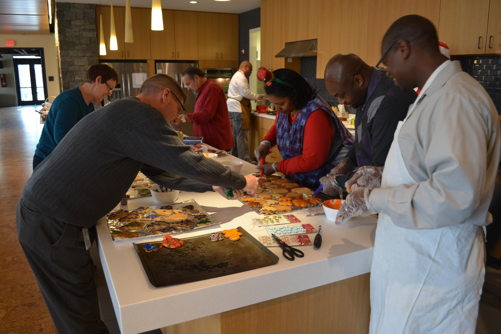 From left: Bill Farmer (foreground), Judy Durnin, Tony Acosta, Reggie Burks (at rear counter), Dorothy Russell, Derrick Washington and George Gray of DLA Logistics Operations' Disposal Policy and Compliance Division bake cookies at the USO Metro Warrior and Family Center, Fort Belvoir, Virginia, Dec. 21, 2016.