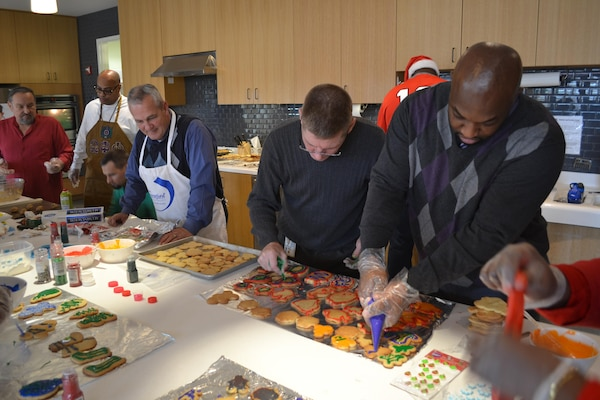 From left: Tony Acosta, Reggie Burks, Mike Johnson, Dennis Ross, Bill Farmer, James Reed (rear, in Santa hat) and Derrick Washington decorate cookies to be distributed Dec. 24 for the USO's annual Christmas Eve 'cookie run,' Fort Belvoir, Virginia, Dec. 21, 2016.