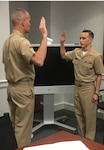 Navy Capt. Harry Thetford, commander of DLA Distribution Norfolk, Va., administers the officer's oath of office prior to Navy Lt. j.g. Jacob Nguyen being promoted to lieutenant.
