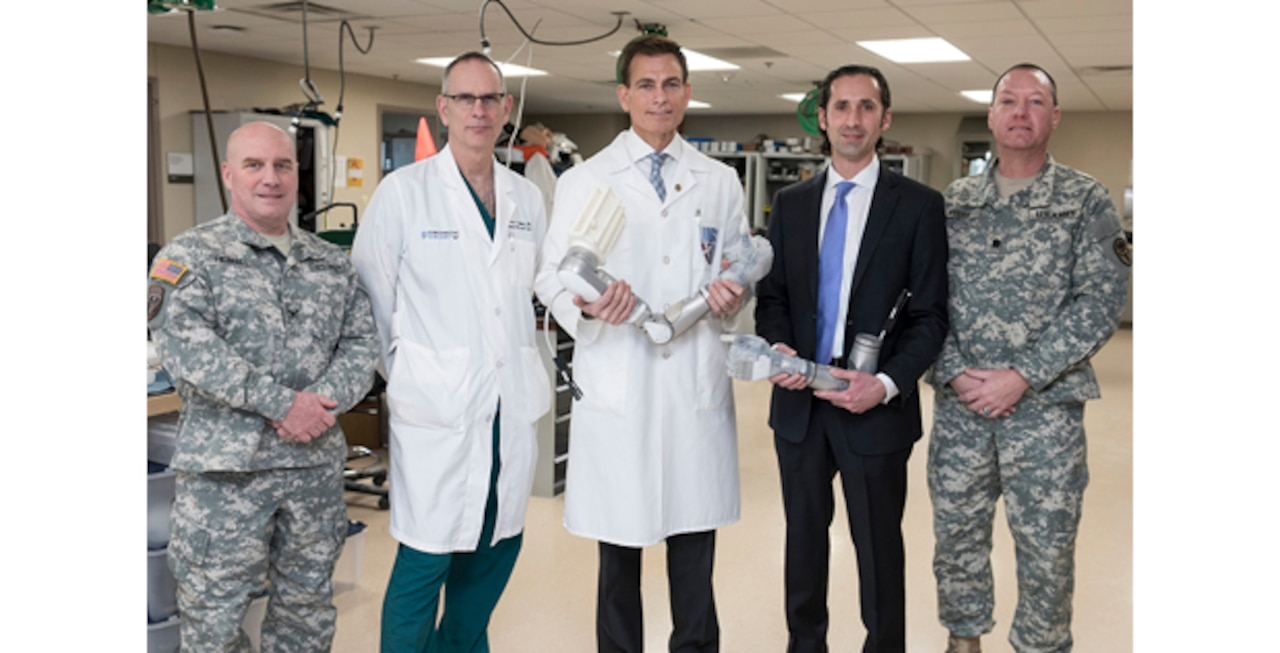 From left, Army Col. Michael Heimall, director of Walter Reed National Military Medical Center in Bethesda, Md.; Air Force Col. (Dr.) Jeffrey Bailey, Walter Reed's director for surgery; Dr. Paul Pasquina, Walter Reed's chief of orthopedics and rehabilitation; Dr. Justin Sanchez, director of the Defense Advanced Research Projects Agency's Biological Technologies Office; and Lt. Col. (Dr.) Keith Myers, director of Walter Reed's Amputee Clinic, pose for a photo at Walter Reed following a ceremony marking the delivery of a groundbreaking upper-limb prosthesis, Dec. 22, 2016. DoD photo
