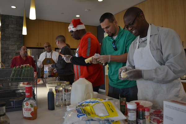 From left: Tony Acosta, Reggie Burks, Bill Farmer, James Reed, Mike Johnson and George Gray prepare the ingredients for cookies the team made from scratch Dec. 21, 2016, at the USO Warrior and Family Center, Fort Belvoir, Virginia.