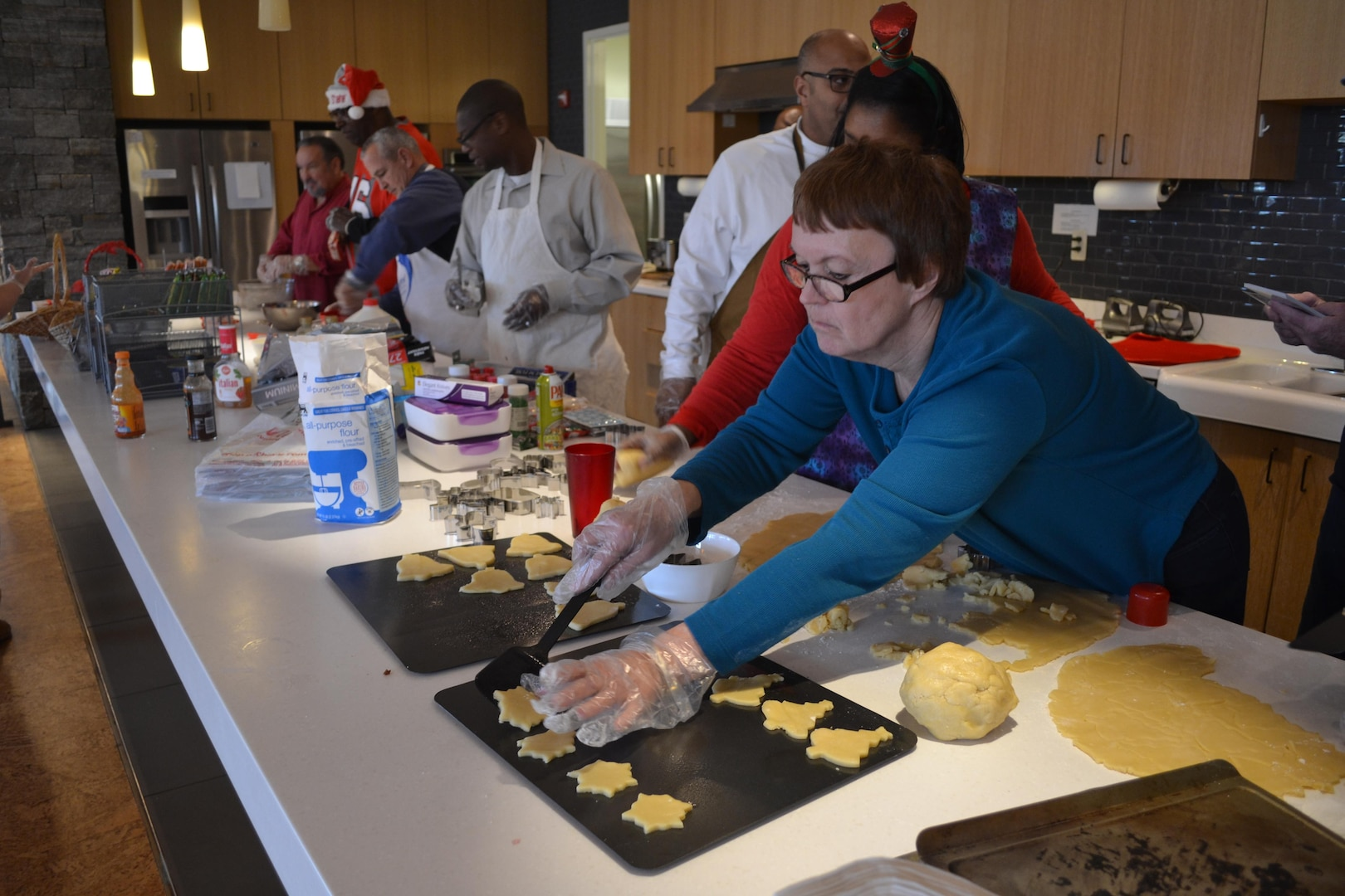 Judy Durnin places newly formed cookies on a baking sheet, Dec. 21, 2016, at the USO Warrior and Family Center, Fort Belvoir, Virginia.