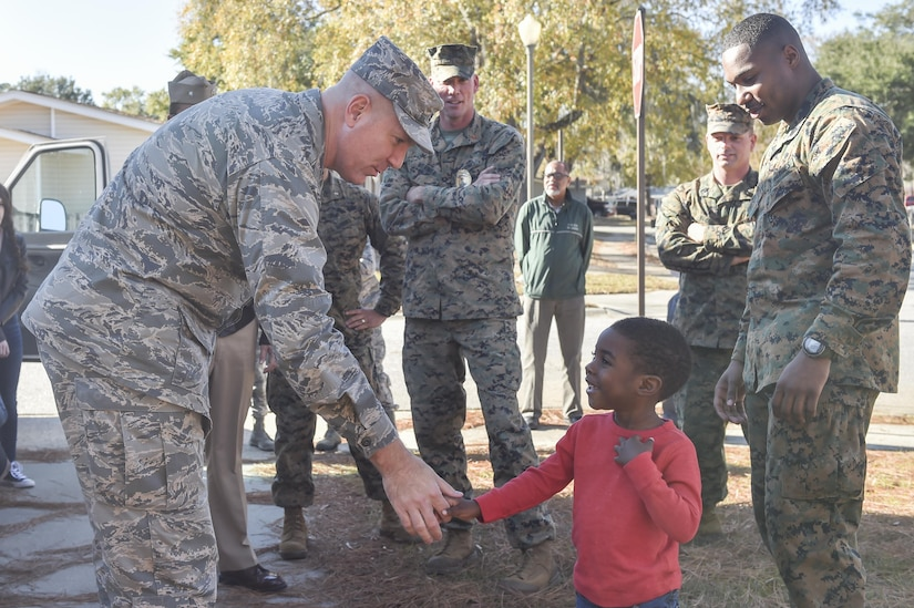 U.S. Air Force Col. Robert Lyman, Joint Base Charleston commander, left, shakes hands with Ruben Barnett Jr., right, at his new home Dec. 21, 2016. Barnett and his son lost all of their belongings in a house fire the day before Thanksgiving.