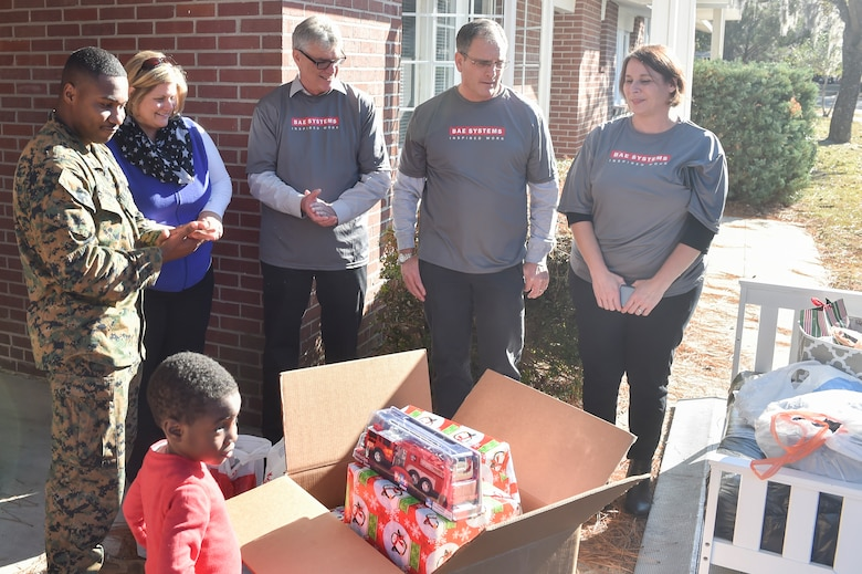 U.S. Marine Staff Sgt. Ruben Barnett, U.S. Naval Consolidated Brig Charleston correctional specialist, and his son, Ruben received gifts from BAE Systems at his new home Dec. 21, 2016. Barnett and his son lost all of their belongings in a house fire the day before Thanksgiving. BAE Systems and Operation Homefront host a campaign called the Joy of Giving where they sponsor a family in need during the holiday season.