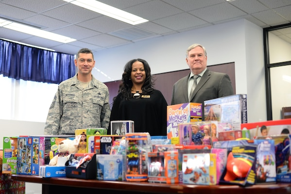 Stephanie Parker, center, director of Fort Lee Army Community Service, accepts a donation of more than 100 toys from the Defense Contract Management Agency. The holiday gifts were delivered Dec. 20 by Air Force Chief Master Sgt. Michael Mitchell, DCMA senior enlisted advisor (left); Richard Fanney, Technical Directorate executive director (right); and Army Lt. Col. Kenneth Darnall, executive officer. (DCMA photo by Stephen Hickok)