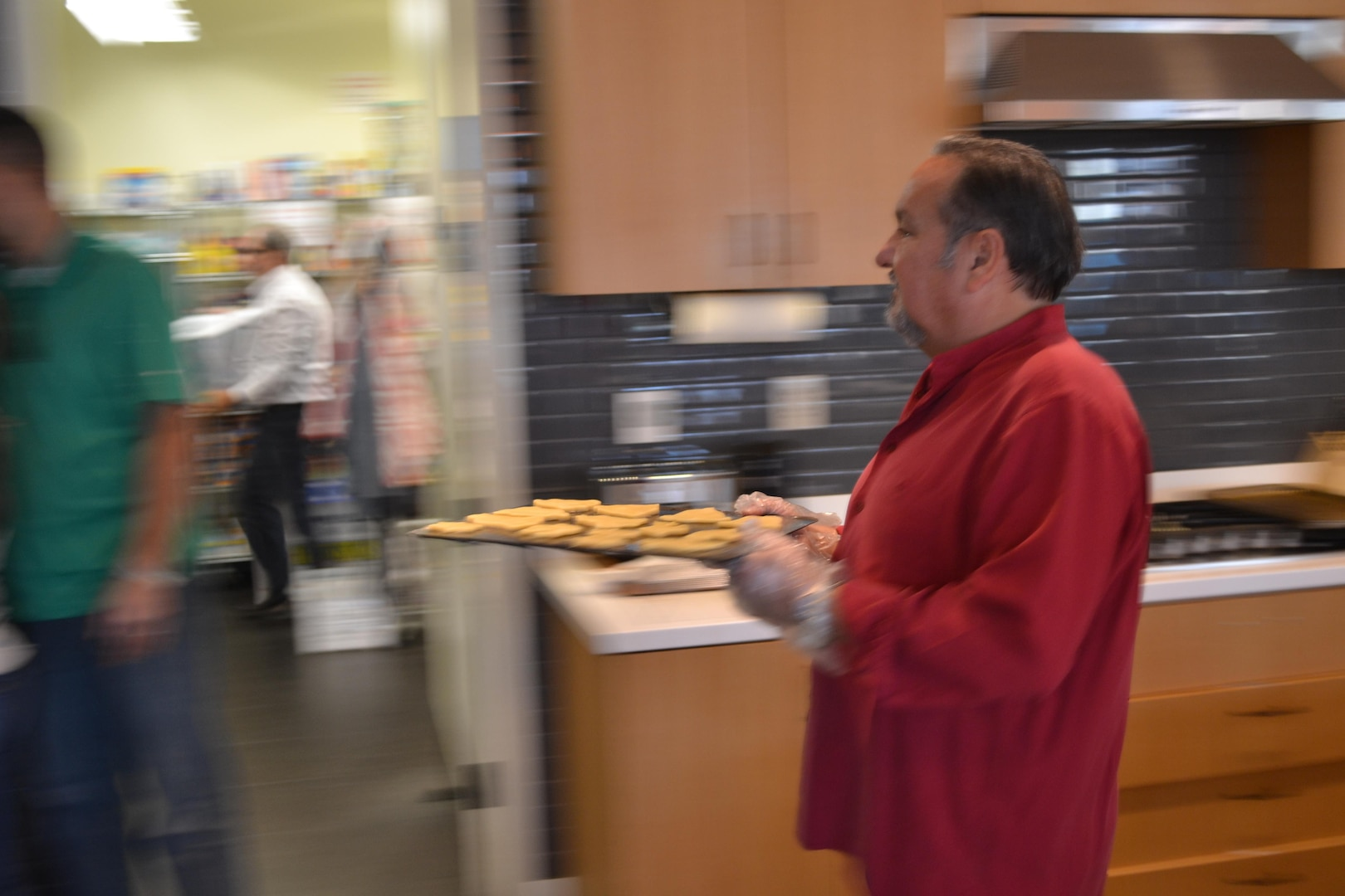 Tony Acosta carries a tray of freshly rolled and shaped cookies to the oven.