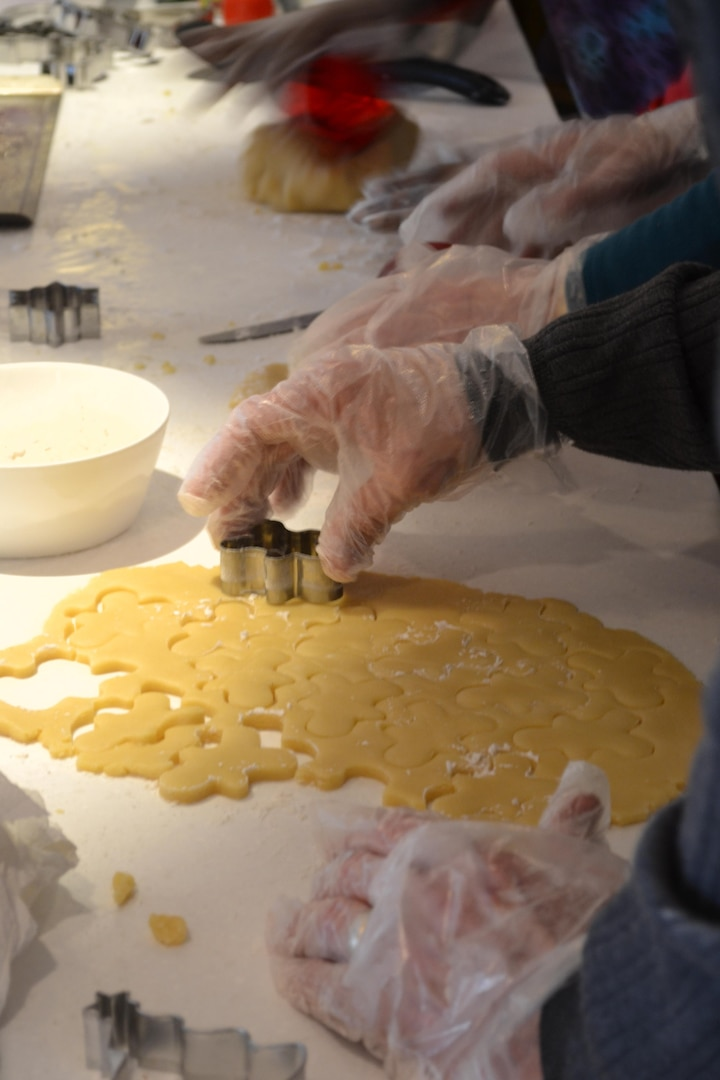 Team members cut freshly kneaded dough into holiday shapes before baking the cookies.