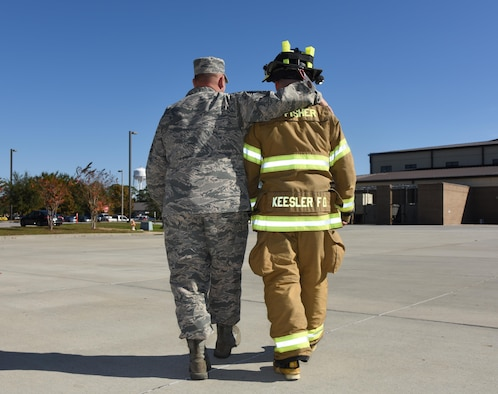 Chief Master Sgt. Anthony Fisher, 81st Training Group superintendent, walks with his son, Senior Airman Tyler Fisher, 81st Infrastructure Division firefighter, Dec. 15, 2016, on Keesler Air Force Base, Miss. After serving at Keesler 3 years ago, Chief Fisher returned after he secured a superintendent position, which placed him at his son's first duty station. (U.S. Air Force photo by Kemberly Groue)