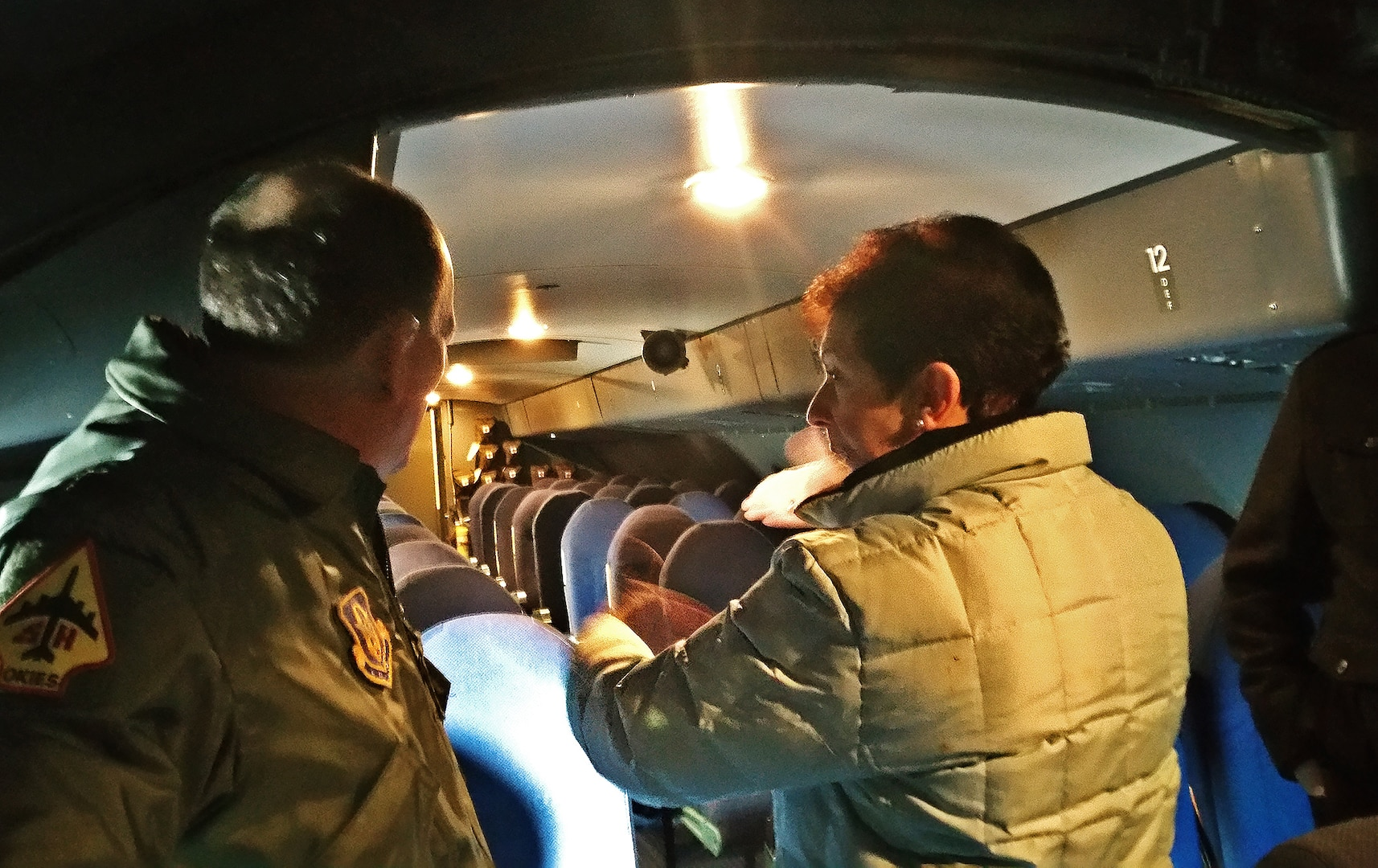 """Retired Col. Regina Aune, right, describes to Col. Thomas K. Smith, 433rd Airlift Wing commander, Dec. 19, 2016, how the children were bedded down in the overhead troop compartment of the aircraft, during """"Operation Babylift."""" Aune was on the first military aircraft to Vietnam to bring the refugees to the United States. """"Operation Babylift"""" was a combined effort between the United States, Canada, Australia and France, to evacuate more than 3,300 refugees from South Vietnam. (U.S. Air Force photo by Minnie Jones)"""