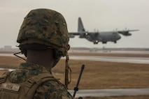 U.S. Marine Corps Staff Sgt. George Price, an Marine Air Traffic Control Mobile Team (MMT) instructor with Marine Air Control Squadron  (MACS) 4 Detachment Bravo, directs a KC-130J Hercules with Marine Aerial Refueler Transport Squadron (VMGR) 152 during a landing as part of aircraft landing zone training at Marine Corps Air Station Iwakuni, Japan, Dec. 21, 2016. The training allows the Marines to gain experience, practice constructing an expeditionary airfield, and complete training and readiness requirements. The MMT Marines conduct this training every three to six months to refine the Marines' skills, keeping them ready for expeditionary operations while in a garrison environment. (U.S. Marine Corps photo by Cpl. Aaron Henson)