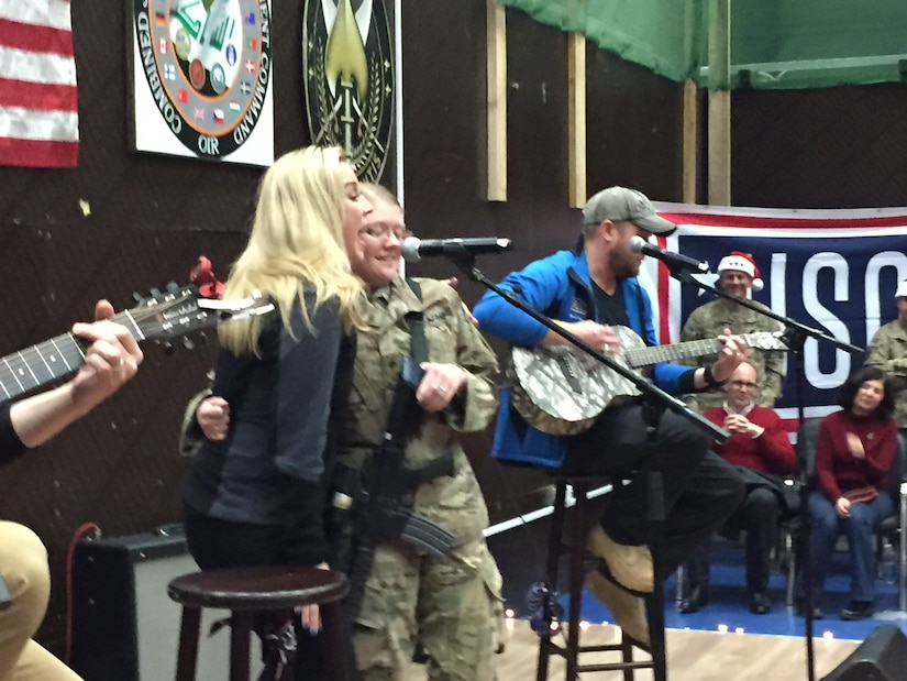 "A 1st Infantry Division soldier sings ""Tough"" with Kellie Pickler during a Dec. 24, 2016, Christmas Eve USO show at Union 3 in Baghdad, Iraq. Marine Corps Gen. Joe Dunford, the chairman of the Joint Chiefs of Staff, brought the show to Iraq to thank service members for their efforts and sacrifices during the holidays. DoD photo by Jim Garamone"