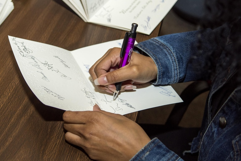 Airman Miranda Loera, 4th Fighter Wing Public Affairs photojournalist, signs holiday cards in Goldsboro, North Carolina, before departing to visit with residents of the North Carolina State Veterans Home in Kinston, North Carolina, Dec. 24, 2016. About 45 volunteers from Seymour Johnson Air Force Base, Goldsboro Elk Lodge #139 and Wayne County passed out handmade goody bags and Christmas cards to the veterans during the holiday visit. (U.S. Air Force photo by Airman Shawna L. Keyes)