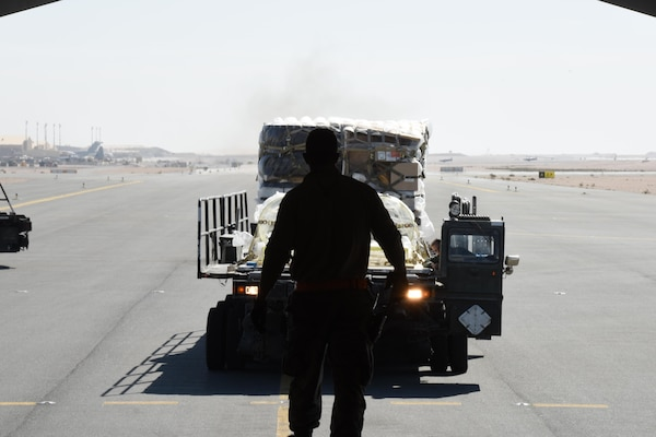 A U.S. Air Force Airman with the 8th Expeditionary Air Mobility Squadron guides an Airman driving a Tunner 60K cargo loader at Al Udeid Air Base, Qatar, Dec. 12, 2016. The 8th EAMS expertise in transportation and logistics enable them to inspect, temporarily store and load cargo such as munitions, blood, special operations cargo, hazardous materials, vehicles and medical supplies. (U.S. Air Force photo by Senior Airman Cynthia A. Innocenti)