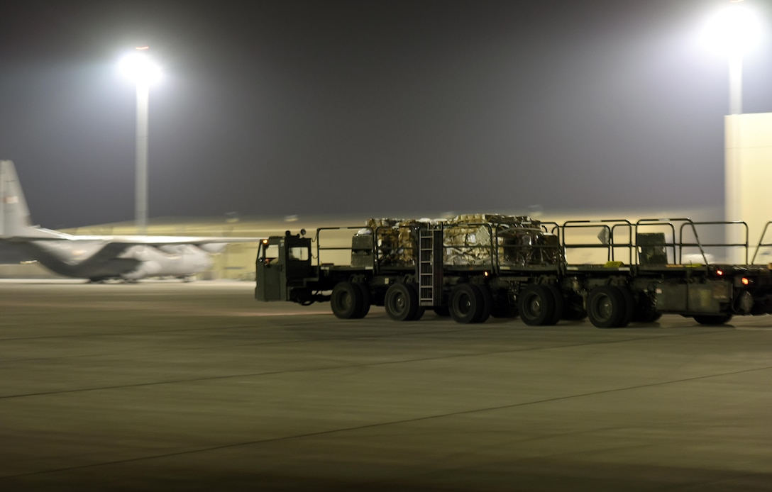 A U.S. Air Force Airman with the 8th Expeditionary Air Mobility Squadron departs from an aircraft driving a Tunner 60K cargo loader at Al Udeid Air Base, Qatar, Dec. 24, 2016. Tunners are used to load and offload heavy cargo, making transport on the flightline quick and efficient. (U.S. Air Force photo by Senior Airman Cynthia A. Innocenti)