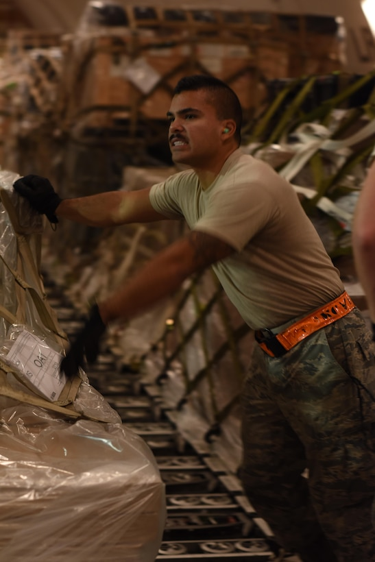 U.S. Air Force Senior Airman Zephaniah Valdez, a ramp services specialist with the 8th Expeditionary Air Mobility Squadron, assists moving cargo onto a Tunner 60K cargo loader at Al Udeid Air Base, Qatar, Dec. 24, 2016. The 8th EAMS expertise in transportation and logistics enable them to inspect, temporarily store and load cargo such as munitions, blood, special operations cargo, hazardous materials, vehicles and medical supplies. (U.S. Air Force photo by Senior Airman Cynthia A. Innocenti)