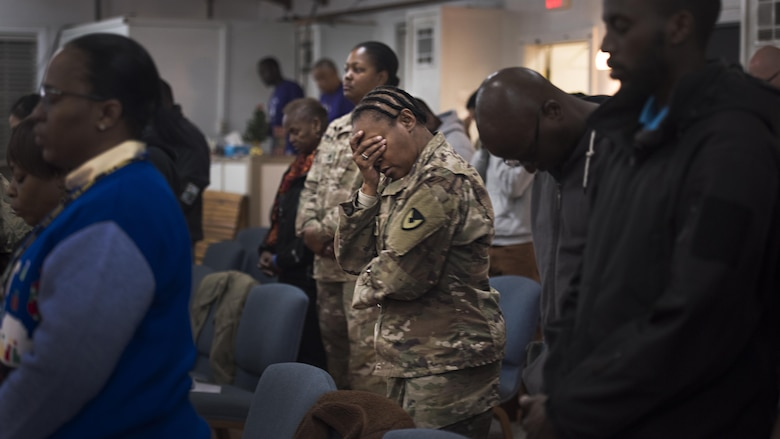 Sgt. Maj. Velma Lyons, Army Field Support Battalion-Afghanistan battalion sergeant major, prays during a Christmas gospel service Dec. 25, 2016 at the Enduring Faith Chapel, Bagram Airfield, Afghanistan. While holidays away from families can be challenging, service members celebrated Christmas by attending church and spending time with friends. (U.S. Air Force photo by Staff Sgt. Katherine Spessa)