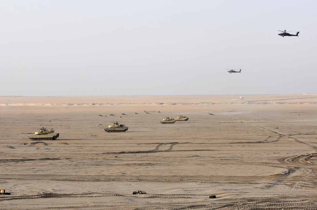 M1A2 Abrams Main Battle Tanks move to engage targets during a joint combined arms live-fire exercise near Camp Buehring, Kuwait Dec. 6-7, 2016. The multi-day exercise was designed to test the efficiency of the U.S. Army and Kuwaiti Land and Air forces abilities to identify and eliminate enemies' anti-aircraft capabilities. Around 30 M1 Abrams Main Battle Tanks, two Kuwaiti AH-64 Apache helicopters, several Bradley Armored Fighting Vehicles, scout sniper teams, 120mm mortar teams, and M109 Self Propelled Howitzer artillery fire assaulted mock enemy positions during the exercise. (U.S. Army photo by Sgt. Aaron Ellerman)