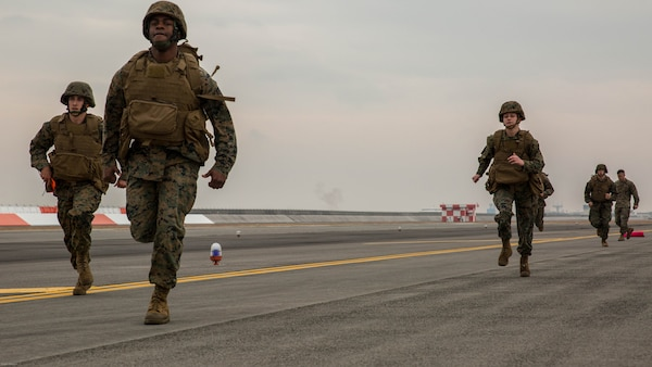 U.S. Marines with Marine Air Control Squadron (MACS) 4 Detachment Bravo, Marine Air Traffic Control Mobile Team (MMT), run to the next 500-foot marker of an expeditionary runway during aircraft landing zone training at Marine Corps Air Station Iwakuni, Japan, Dec. 21, 2016. The training allows the Marines to gain experience, practice constructing an expeditionary airfield, and complete training and readiness requirements. An MMT team comprises of a base, pace, chase, reference, navigation aid and communication technician who establish a runway in remote locations during combat scenarios, medical evacuations or for humanitarian aid.