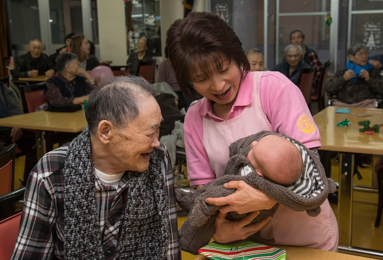 A Japanese elder, left, and Eiko Koiwa, center, a caretaker, smiles at Matthew Joiner, right, son of Master Sgt. James Joiner, a 35th Civil Engineer Squadron explosives ordnance disposal technician, at Harunaoka Old Age Home, Misawa City, Japan, Dec. 22, 2016. Approximately 20 Airmen and their families spent time with members to get them to be active and combat loneliness. As an easy activity, the children brought balloons to bounce back and forth with the Japanese nationals. (U.S. Air Force photo by Airman 1st Class Sadie Colbert)