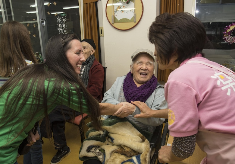 Rachel Skaggs, left, wife of Tech. Sgt. Erik Skaggs, the 35th Medical Group executive officer, shakes hands with Hiromu Ijiri, center, a Japanese elder, and Eiko Koiwa, a caretaker, at Harunaoka Old Age Home, Misawa City, Japan, Dec. 22, 2016. Misawa Air Base's Chapel and its groups visit the facility bi-monthly to spend time with them, ensuring the members are not lonely. The facility provides help for elderly Japanese nationals who have no one to care for them. (U.S. Air Force photo by Airman 1st Class Sadie Colbert)