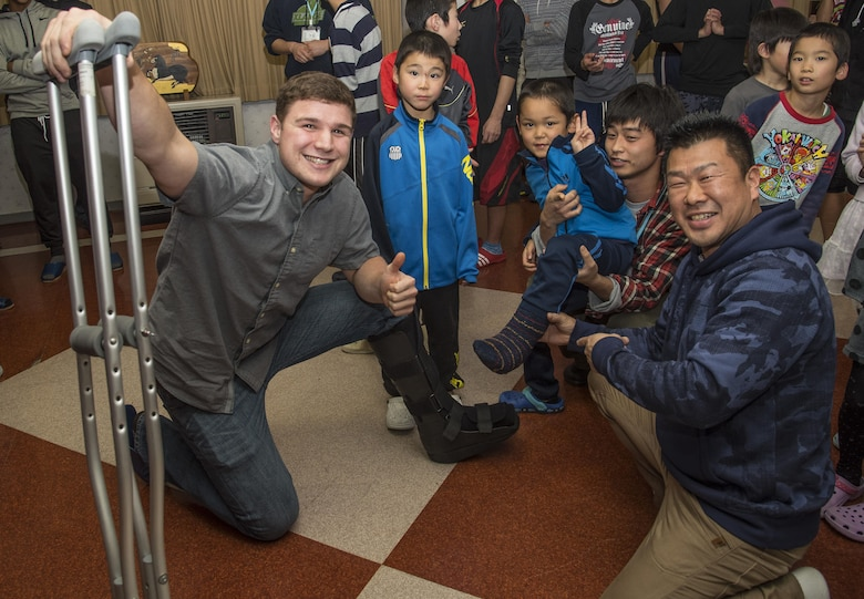 U.S. Air Force Airman Russel Plunkey, left, a 35th Civil Engineer Squadron pavements and equipment technician, poses with Yuussei, a Shichinohe Orphanage member, to show their boots at Shichinohe, Japan, Dec. 23, 2016. The squadron brought gifts to each orphan as well as donated a flat screen TV and a Wii gaming system to the facility. (U.S. Air Force photo by Airman 1st Class Sadie Colbert)