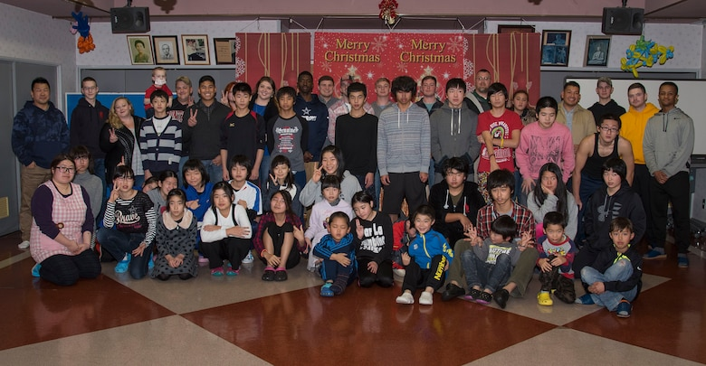 Airmen of the 35th Civil Engineer Squadron pose with Shichinohe Orphanage children at Shichinohe, Japan, Dec. 23, 2016. The squadron wanted to reach out beyond the city limits of Misawa, Japan, by helping those who did not have anyone to celebrate the holidays with. (U.S. Air Force photo by Airman 1st Class Sadie Colbert)
