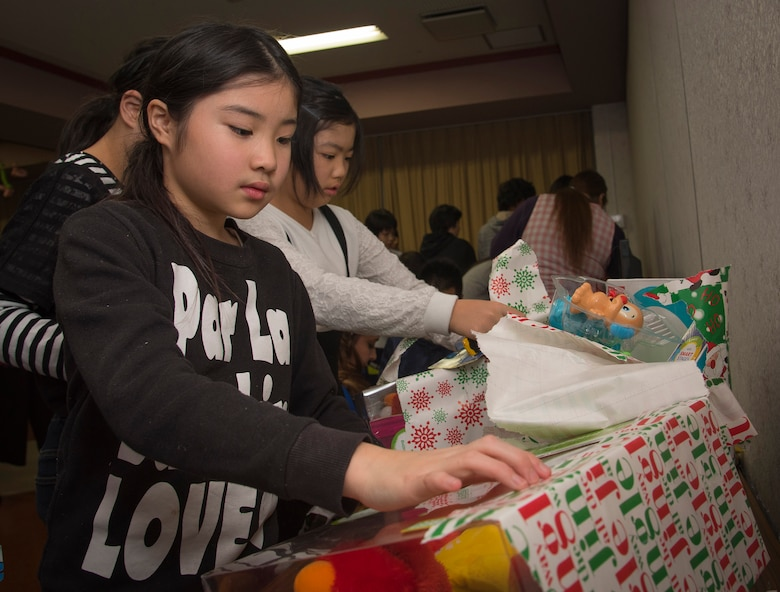 Hoshimi Kohaneo, a Shichinohe Orphange member, unwarps a present received from Misawa Air Force Base Airmen at Shichinohe, Japan, Dec. 23, 2016. The orphanage holds 41 orphans with approximately six caretakers staying overnight to guide them and ensure the group is ready for everyday activities like completing schoolwork. (U.S. Air Force photo by Airman 1st Class Sadie Colbert)