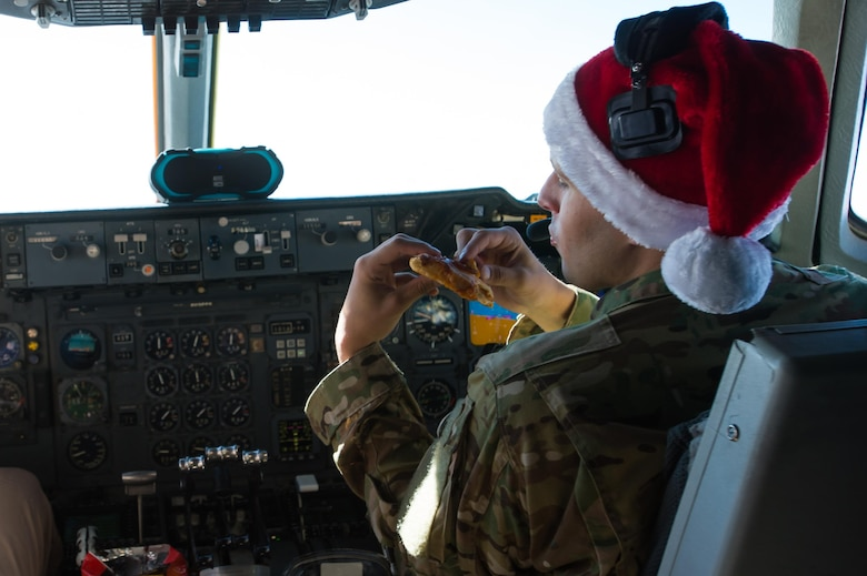 A 380th Air Expeditionary Wing KC-10 Extender pilot, 1st Lt. Andrew, eats reheated pizza during a sortie in support of Combined Joint Task Force-Operation Inherent Resolve over Iraq, Dec. 25, 2016. Crew members used two small ovens to prepare their holiday meal. (U.S. Air Force photo/Senior Airman Tyler Woodward)