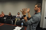 Jarvis Beaver, a business analyst in DLA Energy, uses expressive body language to teach agency students American Sign Language.