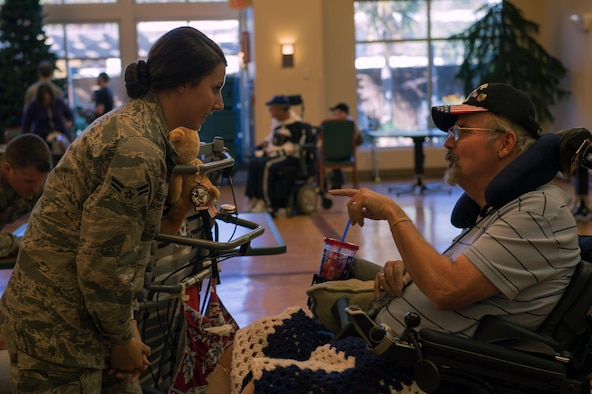 Airman 1st Class Maygan Straight, combat broadcaster with 1st Combat Camera Squadron, Joint Base Charleston, S.C., speaks with retired Air Force Chief Master Sgt. Ron Evans during a visit to the Veterans Victory House, Walterboro, S.C., Dec. 2, 2016. Members of the Air Force Sergeants Association and volunteers gather annually to support local Veterans during the holiday season. (U.S. Air Force Photo by Staff Sgt. Amy Picard)
