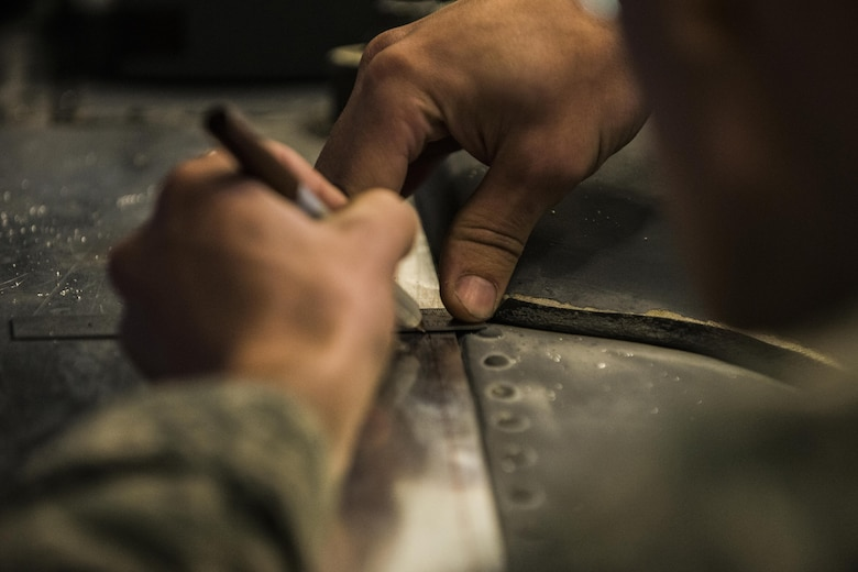 Airman 1st Class Caleb Jackson, 27th Special Operations Maintenance Squadron technician, marks a measurement while restoring areas of a MH-53 Pave Low helicopter Nov. 10, 2016, at Cannon Air Force Base, N.M. The aircraft structural maintenance shop is responsible for repairing and ensuring structural integrity for all aircraft at Cannon. (U.S. Air Force photo by Senior Airman Luke Kitterman/Released)