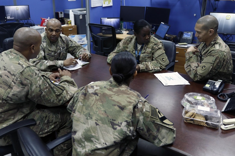 1st Sustainment Command (Theater), Soldiers from the Strategic Operations and Plans Team meet to discuss future operations at Camp Arifjan, Kuwait, Dec. 26.  Communication within the SOaP team plays a key role with so many moving parts from numerous logistical areas of expertise working simultaneously to develop future plans while maintaining current logistical operations in the U.S. Central Command's area of operations.