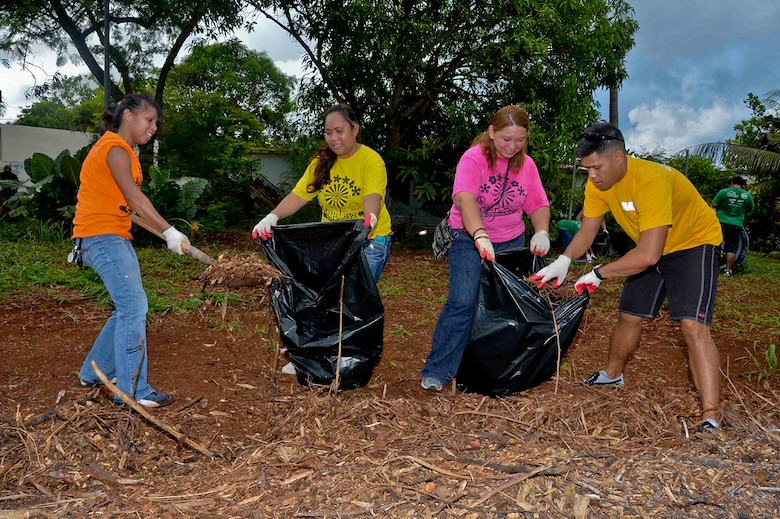 In this file photo, Yeoman 1st Class Erik Estrada, far right, assigned to the submarine tender USS Frank Cable (AS 40), helps local volunteers pack mulch into bags in the village of Dededo, Guam.  Frank Cable Sailors teamed up with volunteers from Island Girl Power, a local community service program for young girls, to clean and renovate a series of parks. Frank Cable, forward deployed to the island of Guam, conducts maintenance and support of submarines and surface vessels deployed to the U.S. 7th Fleet area of responsibility.