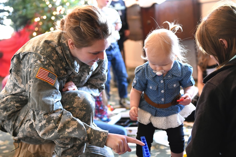 U.S. Army Private Pfc. Emily Shepperd, 316th Psychological Operations Company, helps Emma Thompson with a board game during their annual family day in Kokomo, Ind., Dec. 10, 2016. The event included a special Welcome Home Warrior-Citizen ceremony for returning deployers and a promotion ceremony in addition to holiday festivities for Soldiers and their families. (U.S. Air Force photo/Tech. Sgt. Benjamin Mota)