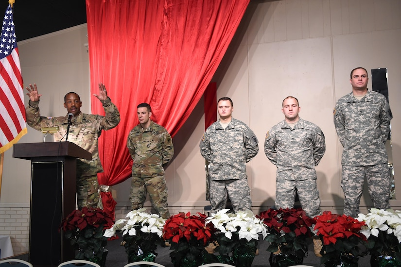From right to left, Sgt. Nathan Richardson, 316th Psychological Operations Company PSYOP sergeant, Sgt. Daniel Hiser, 316th PSYOP Co. PSYOP sergeant and Sgt. Stephen Thompson, 209th Quartermaster Company mechanic, stand in formation as Col. Jesse Manning, 2nd Psychological Operations Group commander, speaks to Soldiers and their families during a promotion ceremony in Kokomo, Ind., Dec. 10, 2016. The ceremony was conducted during a family day event that included a Welcome Home Warrior-Citizen award ceremony followed by holiday festivities. (U.S. Air Force photo/Tech. Sgt. Benjamin Mota)
