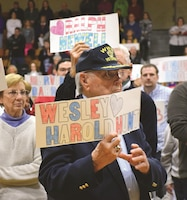 "Jim Sharp, a former 1st Infantry Division Soldier, holds a sign bearing the name of one of the 101 Riley County men who lost his life during World War II during ""Taps"" at the end of the Pearl Harbor Day concert Dec. 7 at the Peace Memorial Auditorium in Manhattan, Kansas. The auditorium serves as a living memorial for those men."